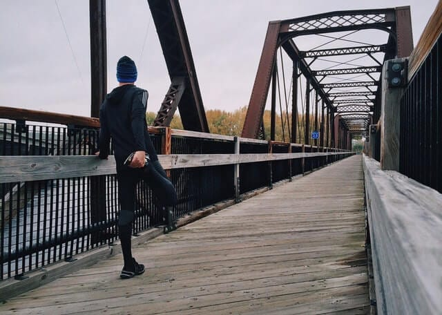 Runner wearing black clothes on the bridge