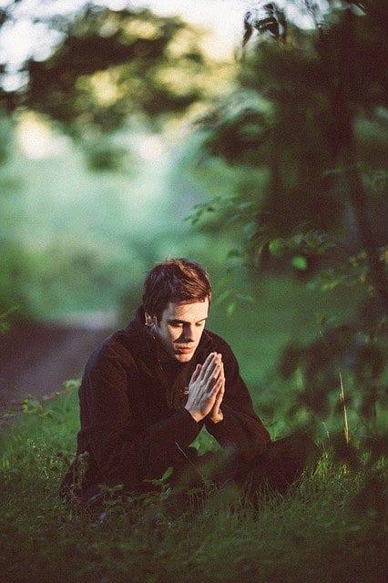 Man praying in the woods