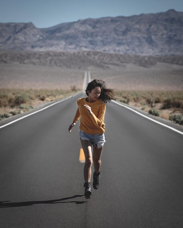 girl running on the road in the middle of desert