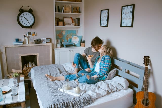 image showing two young adults kissing in bed
