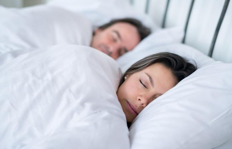 man and woman resting on waterbed