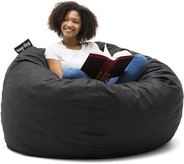 Happy girl reads a book on Big Joe Large Fuf