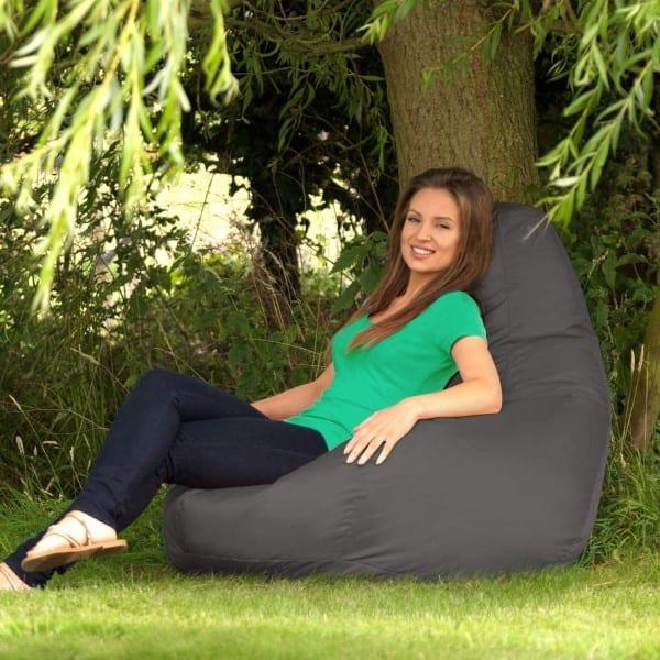Woman wearing green shirt sits on Bazaar Recliner Gaming Bean Bag outdoors
